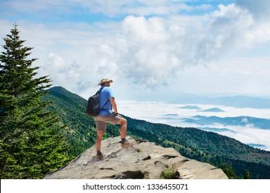 Man on hiking trip, standing on top of the mountain over the clouds, enjoying beautiful summer mountain scenery. Man  looking at beautiful view. Blue Ridge Mountains, North Carolina, USA.