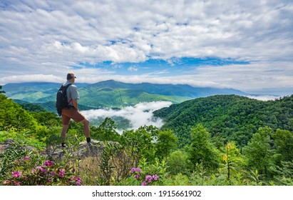 Man on hiking trip, standing on top of the mountain over the clouds, enjoying beautiful summer mountain scenery. Hiker looking at beautiful view. Blue Ridge Mountains, North Carolina, USA. - Shutterstock ID 1915661902