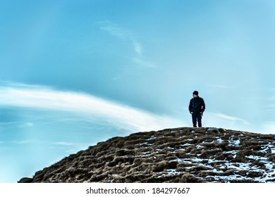 Man on a hill looking away thinking under the cloudy sky