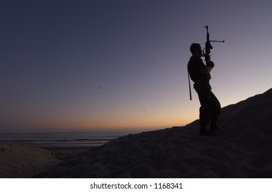man on hill with machine gun
