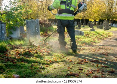 Man on his back working with vest and one gas string trimmer cutting the grass in a graveyard