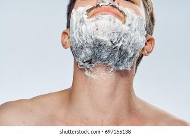 A man on his beard, shaving foam on a gray background, beauty, skin care