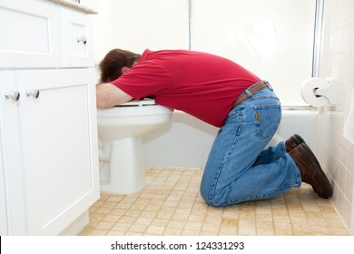 Man on his knees in the bathroom, vomiting into the toilet.