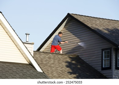 Man on his roof power washing his house.