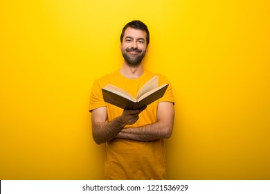 Man on isolated vibrant yellow color holding a book and giving it to someone