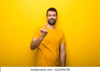 Man on isolated vibrant yellow color showing and lifting a finger