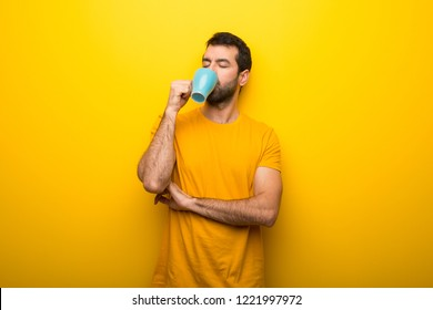 Man on isolated vibrant yellow color taking a coffee in takeaway paper cup and smiling because he will start the day well
