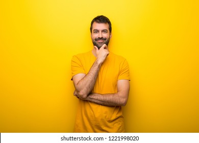 Man on isolated vibrant yellow color smiling and looking to the front with confident face