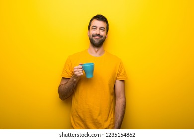 Man on isolated vibrant yellow color holding hot coffee in takeaway paper cup