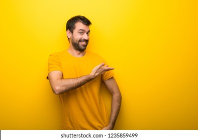 Man on isolated vibrant yellow color pointing back and presenting a product