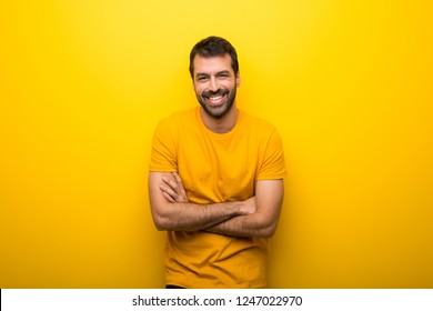 Man on isolated vibrant yellow color keeping the arms crossed while smiling