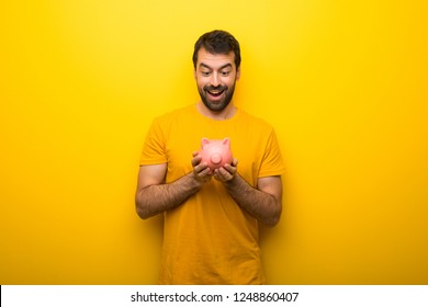 Man on isolated vibrant yellow color holding a big piggybank