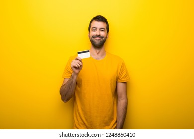 Man on isolated vibrant yellow color holding a credit card