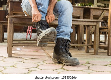 man on jeans is getting dressed his boots