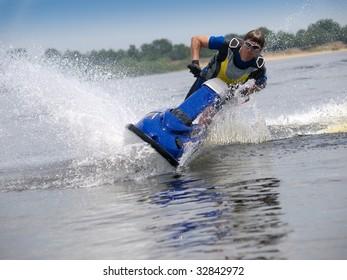 Man on jet ski in the river skims along camera