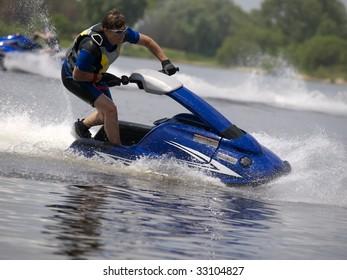 Man on jet ski in the river skim along very fast