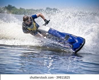 Man on jet ski turns with much splashes