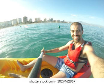 Man on a kayak in Spain taking a selfie. Young man with personal point of view action camera, having fun in a canoe on the water. Summer and sport concepts