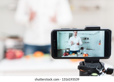 Man on the kitchen filming video. Vlogging concept.