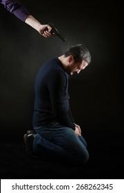 A man on the knees under the gun