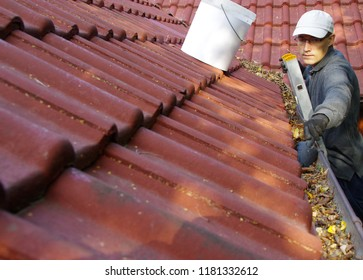 The man on ladder cleans the gutters on the roof. Spring and autumn problem with leaves in gutter.