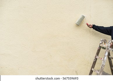 Man on ladder painting with roller an house wall.