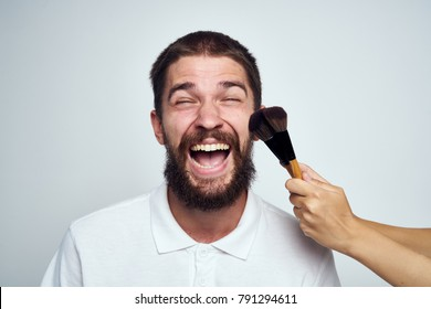 man on a light background with makeup brushes
