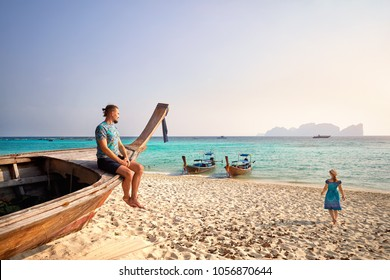 Man on the long tail boat and women walking to the sea on the tropical beach of Phi Phi island in Southern Thailand. Travel magazine concept.