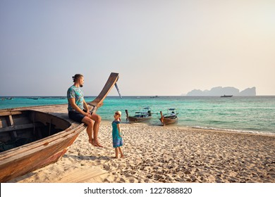 Man on the long tail boat and young women walking near on the tropical beach of Phi Phi island in Southern Thailand. Travel magazine concept.