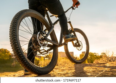 Man on mountain bike. Bicycle wheels close up image on sunset. Low angle view of cyclist riding mountain bike. Foot on pedal.