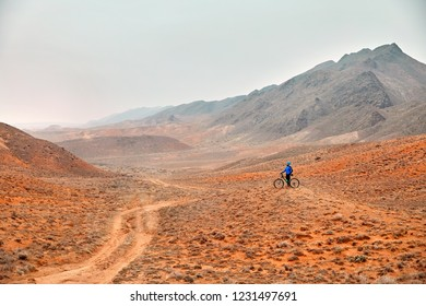 Man on mountain bike in blue shirt in the red desert