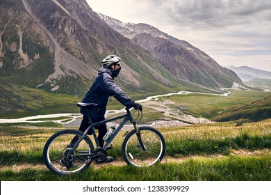Man on mountain bike in helmet in the mountain valley with river at cloudy sky background.