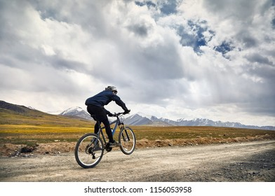 Man on mountain bike rides on the road in the high mountains against blue sky background.