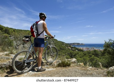 Man on mountain bike with view of Mediterranean sea in north east Spain