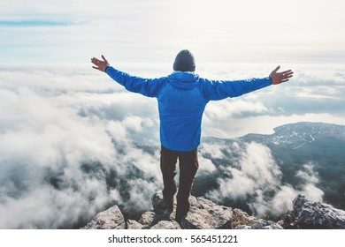 Man on mountain cliff enjoying aerial view hands raised over clouds Travel Lifestyle success concept adventure active vacations outdoor freedom emotions