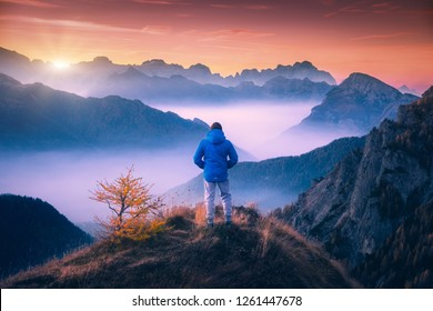 Man on the mountain peak looking on mountain valley with low clouds at colorful sunset in autumn in Dolomites. Landscape with traveler, foggy hills, forest in fall, beautiful sky at dusk in Alps