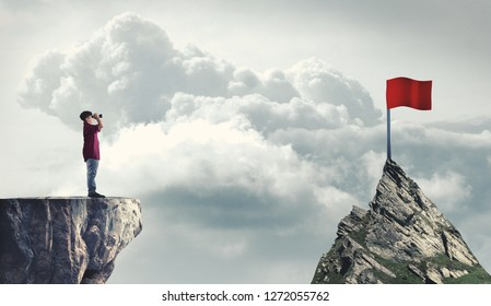 Man on a mountain peak looking through binoculars to a red flag. The concept of reaching goals.