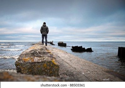 A man on the old broken pier starring at the restless Sea