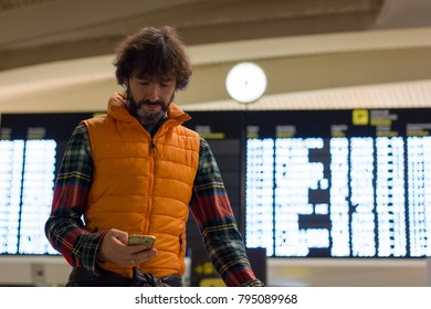 Man on orange puffer vest looking at cellphone with flight schedule board behind at airport. Passenger checking smart phone on arrival, departure lounge