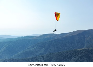 Man on paraglider is flying in the air using a parachute over the mountains behind the blue sky. Extreme sports and freedom