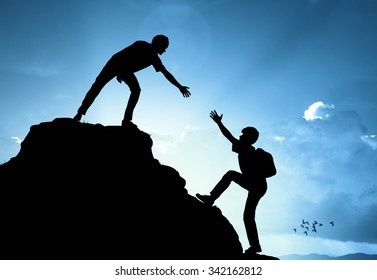 Man on peak mountain climbing helping on sunset background  teamwork  success winner business concept