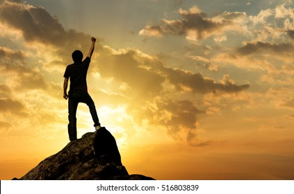 Man on the peak of mountain and sunlight outdoor on nature , success winner business concept