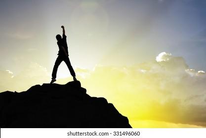 Man on the peak of mountain and suntlight  , success,winner concept