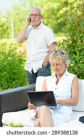 a man on phone and his wife on  computer outside