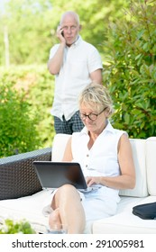 a man on phone and his wife on  computer in their garden