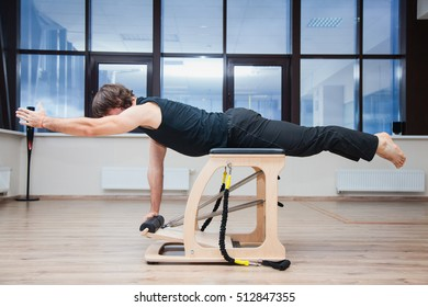 Man on pilates equipment. Fit and slim. Body balance exercise. Lifting left arm