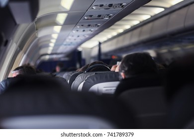 A man on a plane is listening to music with headphones. He is sitting in his seat and only the top of his head is seen from behind.