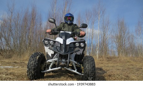 Man on a quad bike, in the background of nature