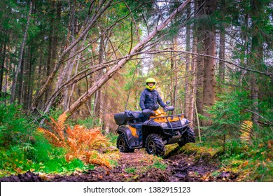 Man on a quad bike in the forest. Riding a quad bike. A man riding an all-terrain vehicle. Off-road riding on an ATV. Active sports. Extreme. Quad bike rental.