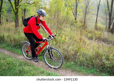 Man on a red bicycle riding at the park